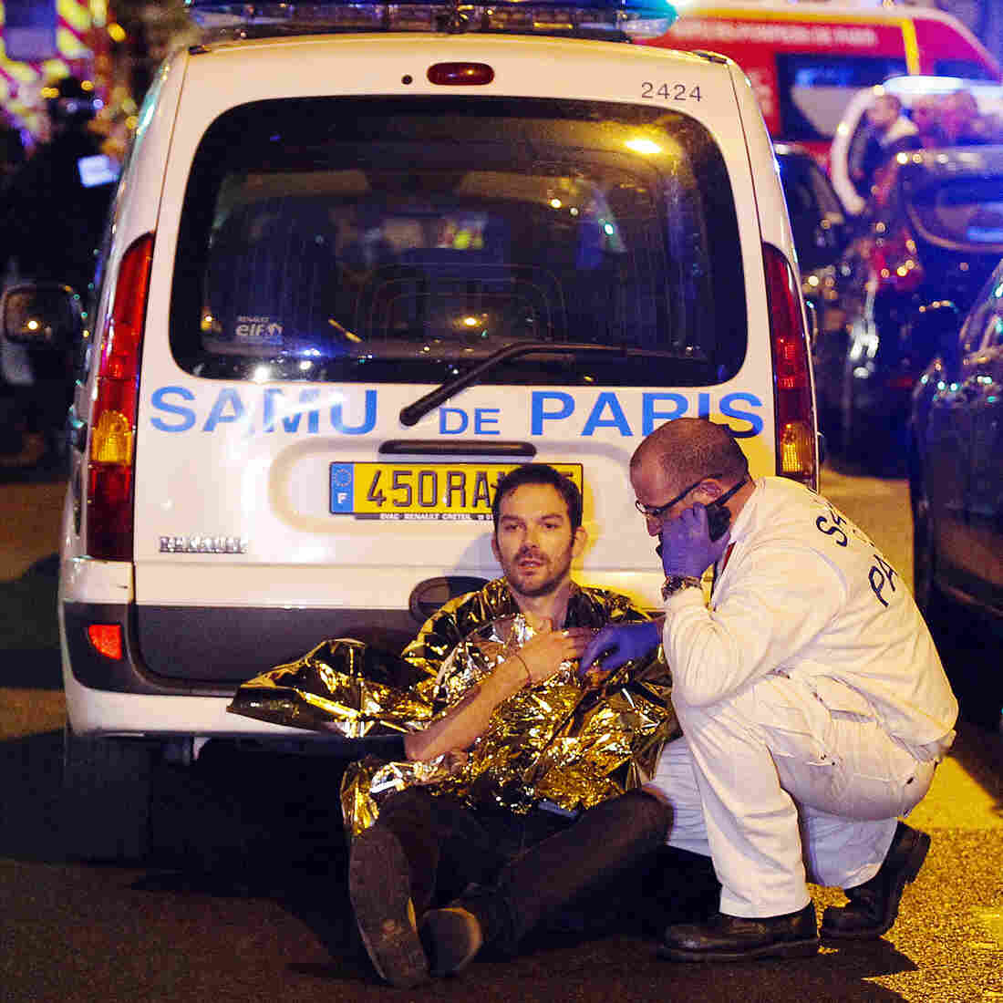A medic tends to a man injured in the terror attacks in Paris on Friday evening. The Islamic State has claimed responsibility for the coordinated assault that has claimed more than 120 lives.