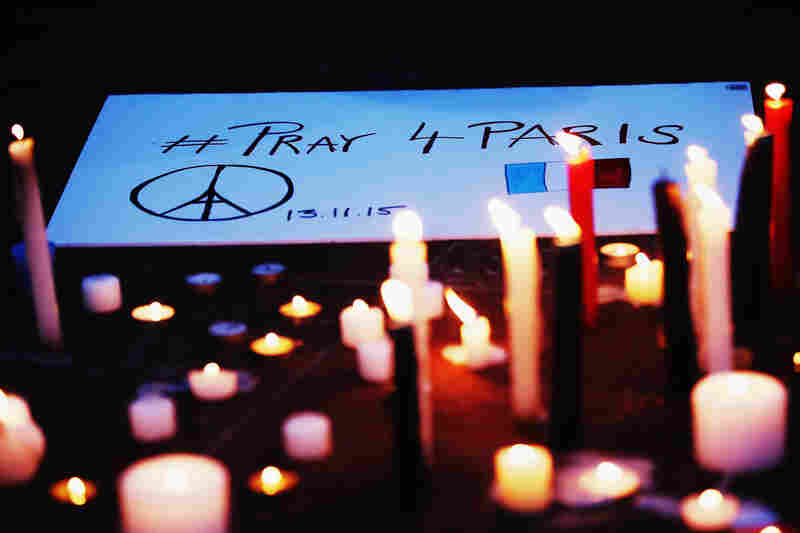 A Peace for Paris sign rests by a series of candles in remembrance of victims of the Paris attacks, in Auckland, New Zealand, on Saturday.