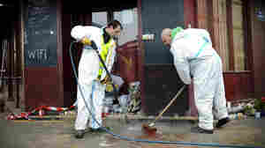 Municipal employees clean the exterior the Carillon cafe, one day after a terrorist attack hit Paris. ISIS has claimed responsibility for the deadly violence.