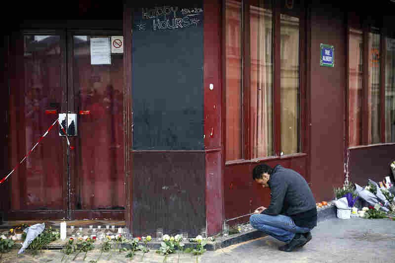 A man places a candle in front of the Carillon cafe. Dozens were reportedly killed on the sidewalks outside the cafe and neighboring bars in this working-class part of central Paris.