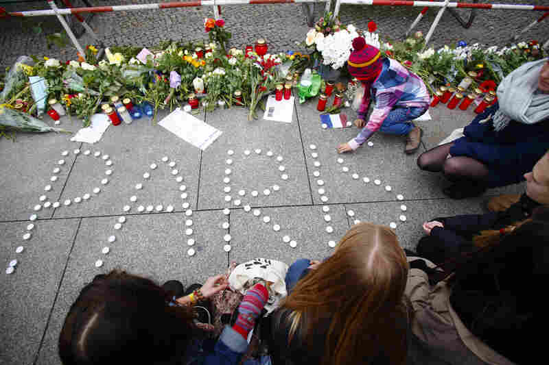 In Germany, people place candles outside the French Embassy in Berlin.