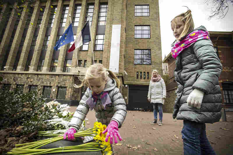 Children place flowers in tribute for the victims of the attacks in front of the French Embassy in The Hague, Netherlands.