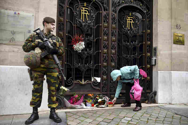 In Belgium, a woman places flowers at France's embassy in Brussels.