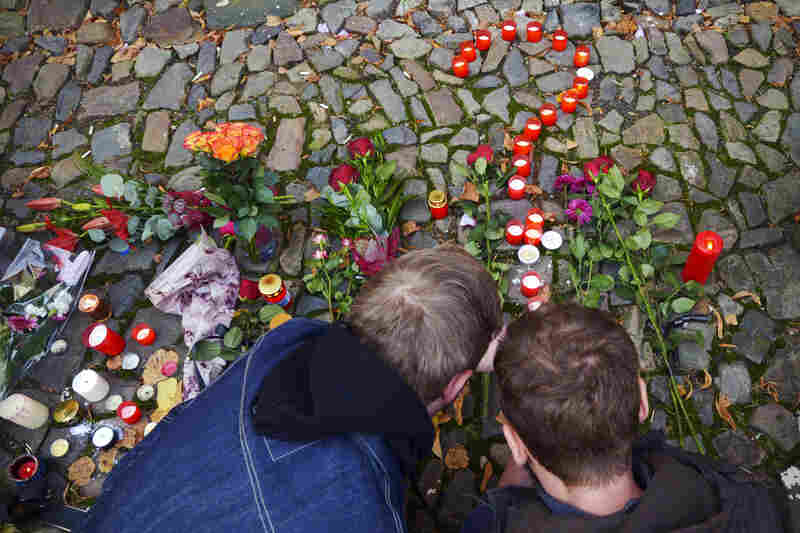 Men place candles in front of the French Embassy in Prague, Czech Republic.