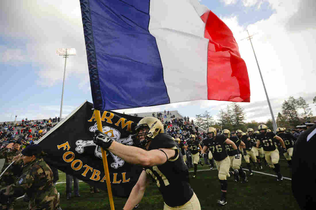 Army defensive back Caleb McNeill carries the French flag onto the field before an NCAA college football game against Tulane in West Point, N.Y.
