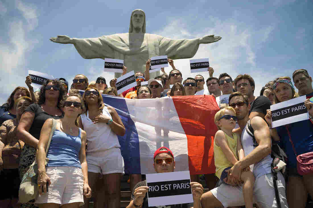 """People hold up a France national flag and signs that read """"Rio is Paris,"""" during a demonstration in front of Christ the Redeemer statue, in Rio de Janeiro, Brazil."""