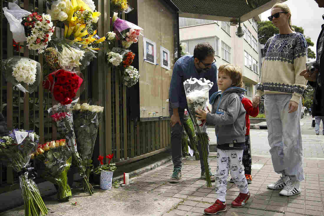 People lay flowers in tribute at the entrance of the French Embassy in Bogota, Colombia.
