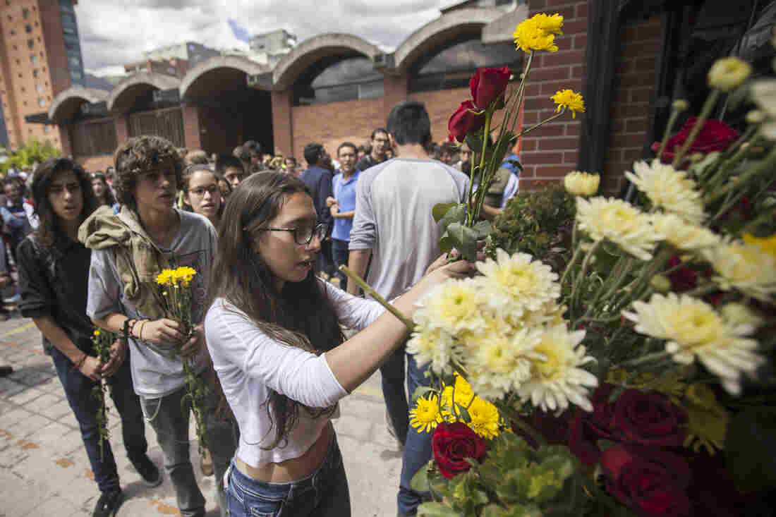 A woman in front of the Alliance Francaise building in Quito, Ecuador, leaves a bouquet of flowers at a tribute to victims of the Paris attacks.