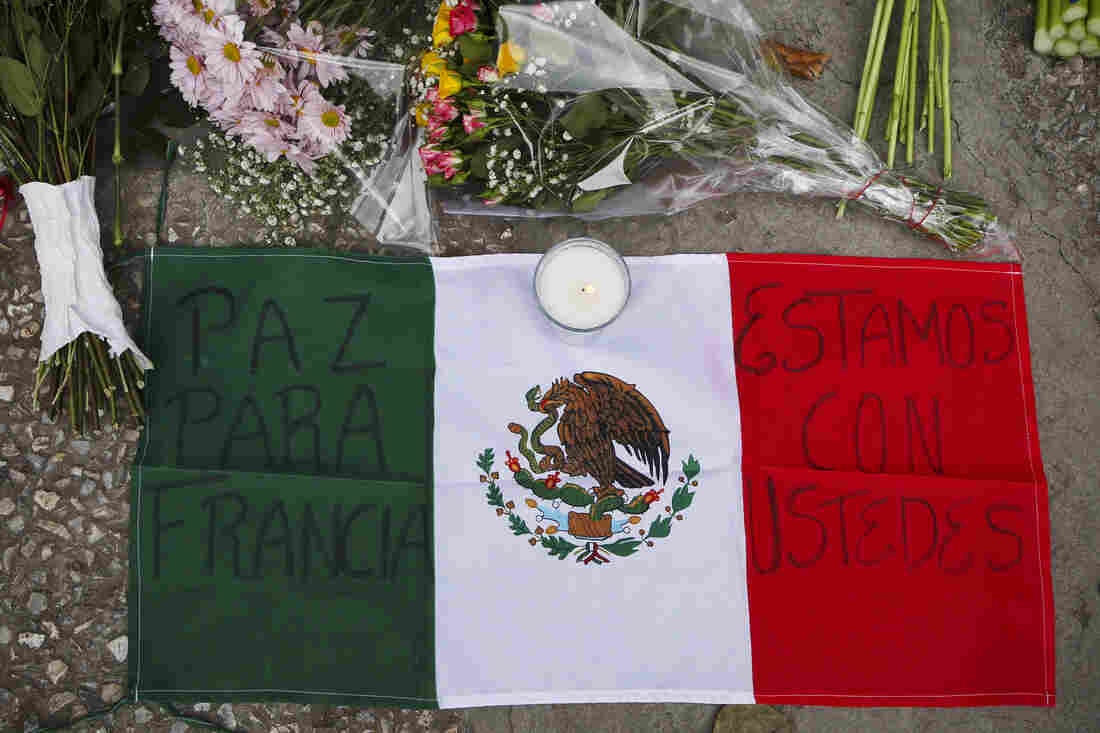 """A Mexican flag reading """"Peace for France"""" and """"We are with you,"""" is one of the many tributes in front of the French Embassy in Mexico City, Mexico."""