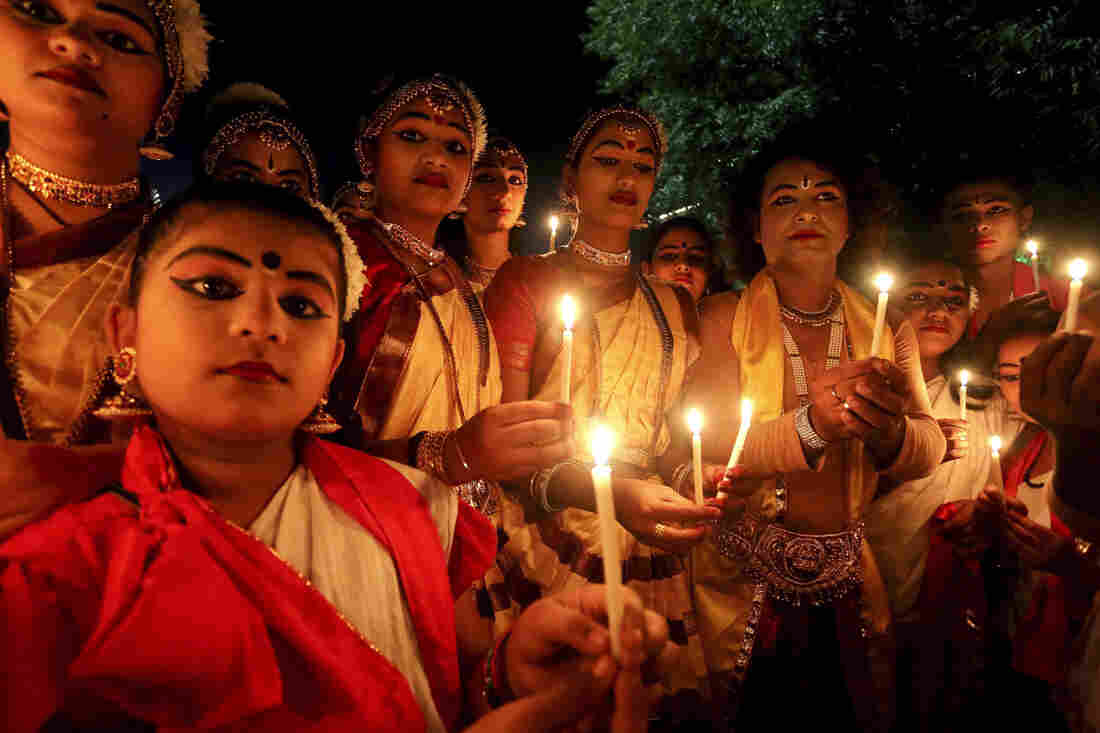 Indian artists dressed to participate in a cultural program hold a candlelight vigil for the victims of the Paris terrorist attacks before performing on stage in Bhopal, India.