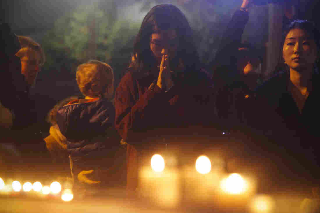 South Korean women pray during a vigil outside the French Embassy in Seoul, South Korea.