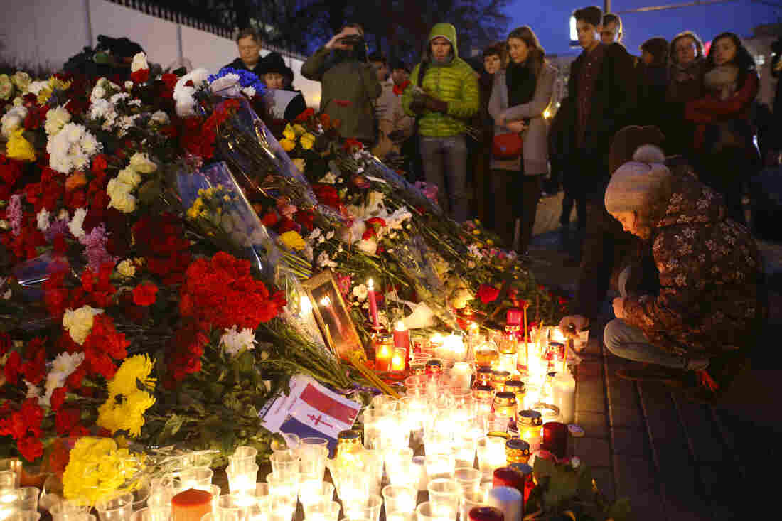 People lay flowers and light candles outside the French Embassy in Moscow, Russia.