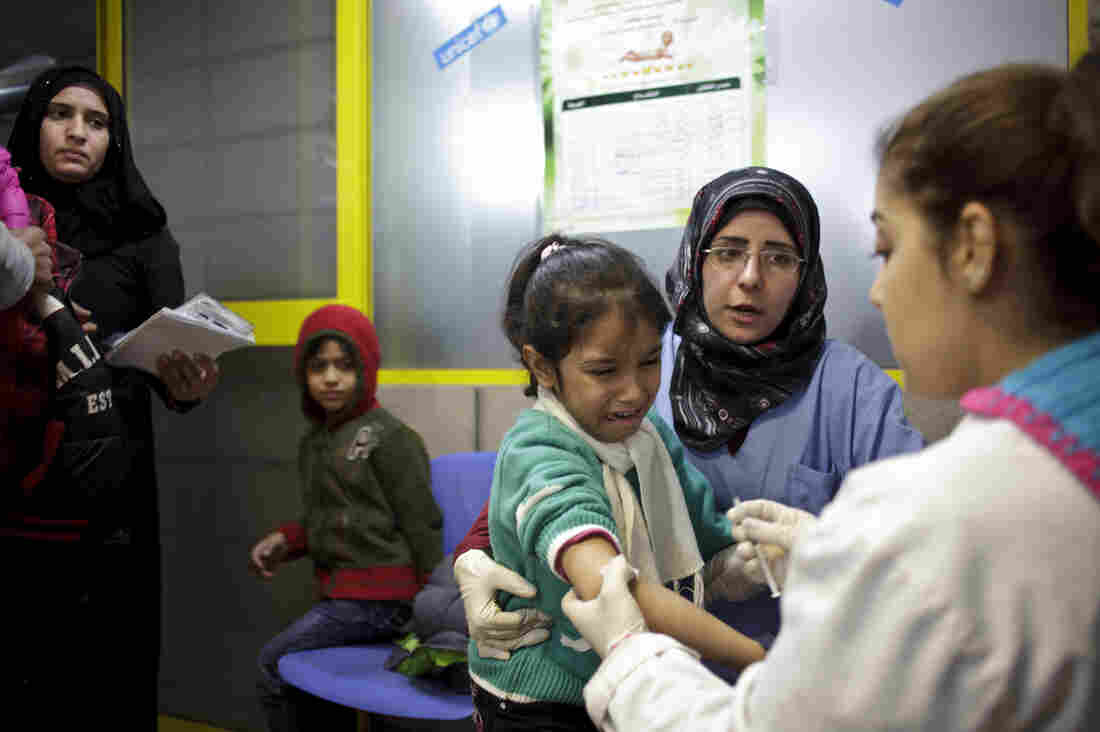 A UNICEF nurse gives the measles vaccine to a Syrian child in a refugee center in Lebanon.