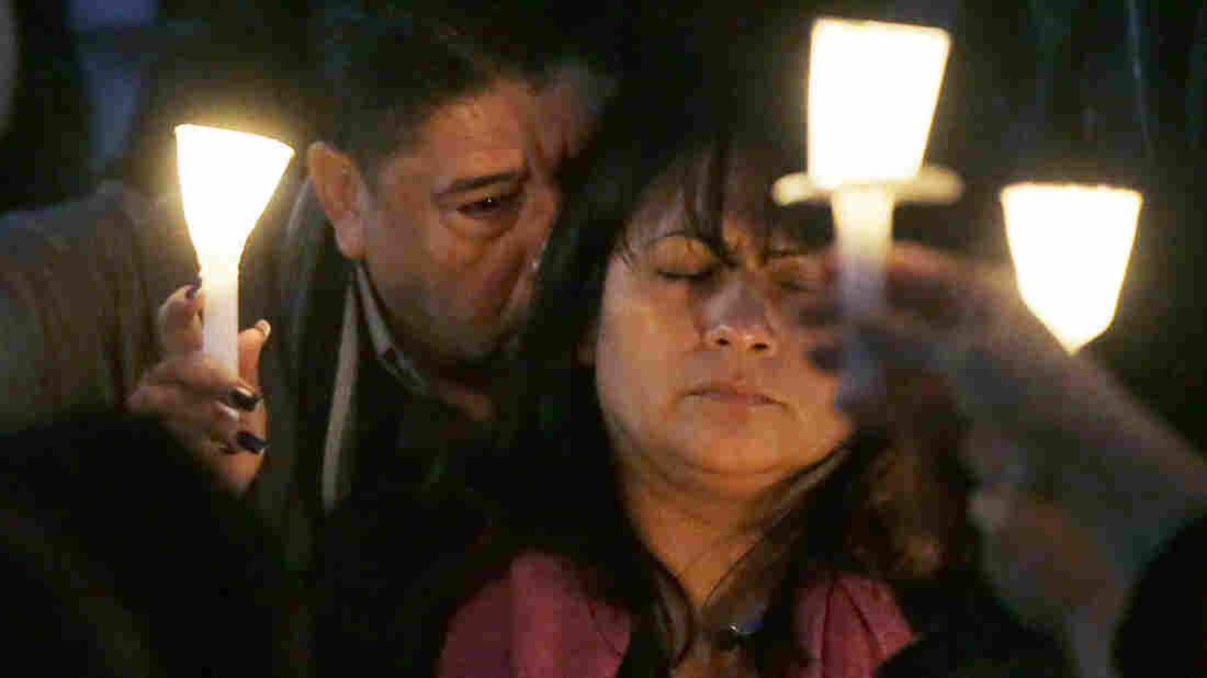 Beatriz Gonzalez, mother of Nohemi Gonzalez, holds up a candle with Nohemi's step-father, Jose Hernandez, during a memorial service Sunday in Long Beach, Calif. Gonzalez was killed at a restaurant in Paris on Friday night during the terrorist attacks.
