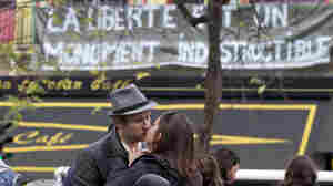 """Two mourners kiss outside the Bataclan concert hall, one of the sites of Friday's terrorist attacks in Paris, now adorned with a banner reading """"Freedom is an indestructible monument."""""""