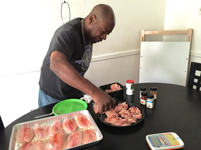 Felipa prepares dinner for his family at their home in West Baltimore, Md.
