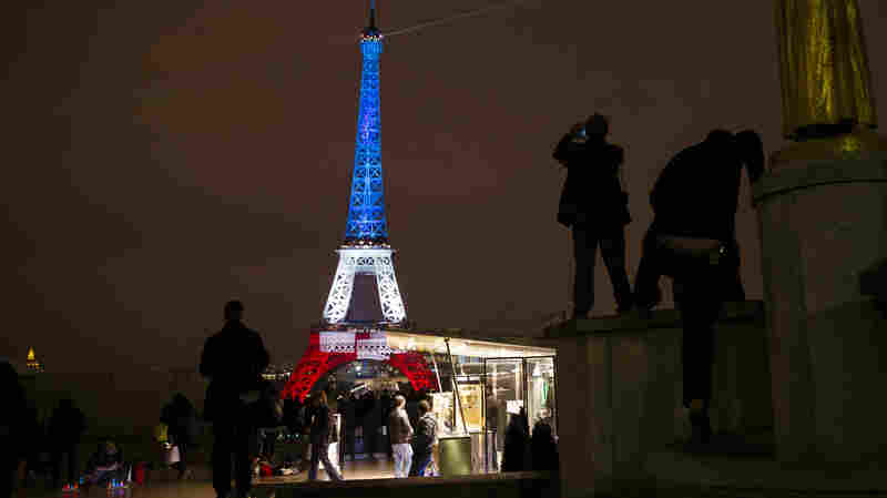 A man takes a picture of the Eiffel Tower illuminated in the French colors in honor of the victims of the attacks on Friday in Paris.