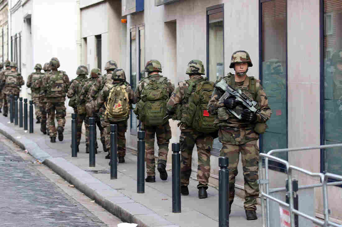 Soldiers patrol a street of Saint-Denis, a suburb of Paris, on Wednesday. Special forces raided an apartment, hunting those behind the attacks that claimed 129 lives in the French capital on Friday.
