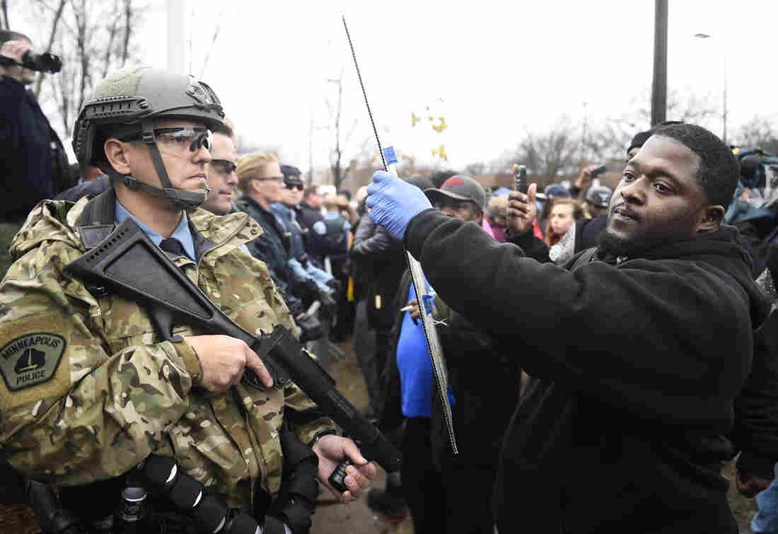 Police officers watch as a demonstrator holds a sign in front of a north Minneapolis police precinct during a protest in response to Sunday's shooting of Jamar Clark by police officers in Minneapolis.