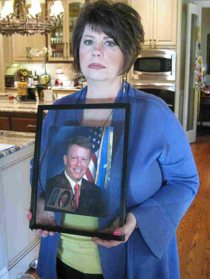 Cathy Costello, holding a picture of her late husband, Mark.