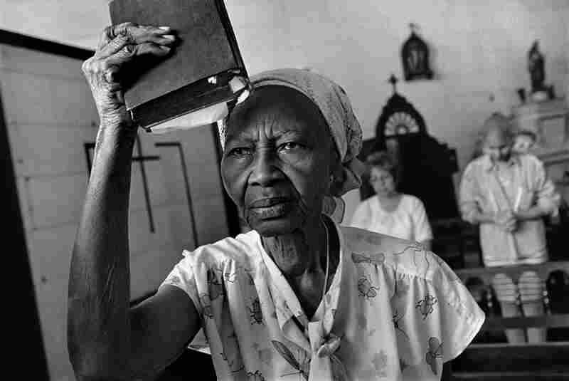 A woman raises her Bible as a flag, before while listening to a sermon in Havana, Cuba in 1997.