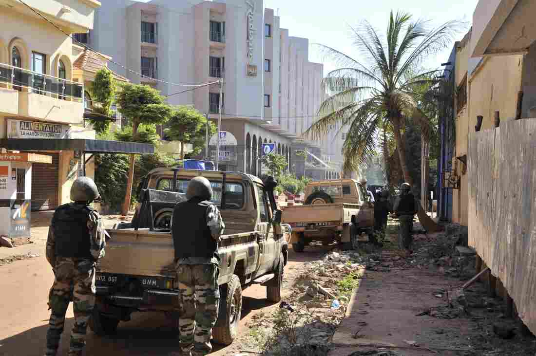 Malian troops take position outside the Radisson Blu hotel in Bamako on Friday. Gunmen went on a shooting rampage at the hotel in the capital of Bamako, seizing 170 guests and staff.