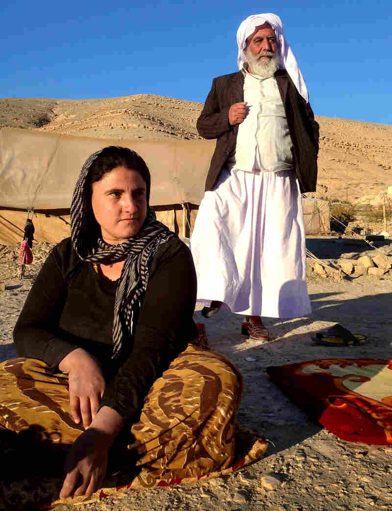 Sevi Zendi, from Iraq's Yazidi minority, says her family sleeps with guns in their tent in case ISIS reaches the exposed encampment. Standing behind her is family patriarch Abdi Ismail, who says that his whole family accepted the decision to stay on Mount Sinjar, passing up the opportunity to escape the ISIS siege when a path was opened.
