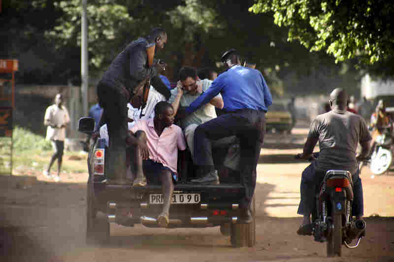 Malian security forces evacuate hostages freed from the Radisson Blu hotel.