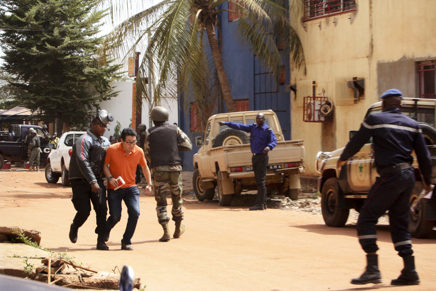 Malian troops assist a hostage to safety near the Radisson Blu hotel in Bamako, Mali, on Friday. Gunmen went on a shooting rampage at the hotel, seizing 170 guests and staff. (Harouna Traore/AP)