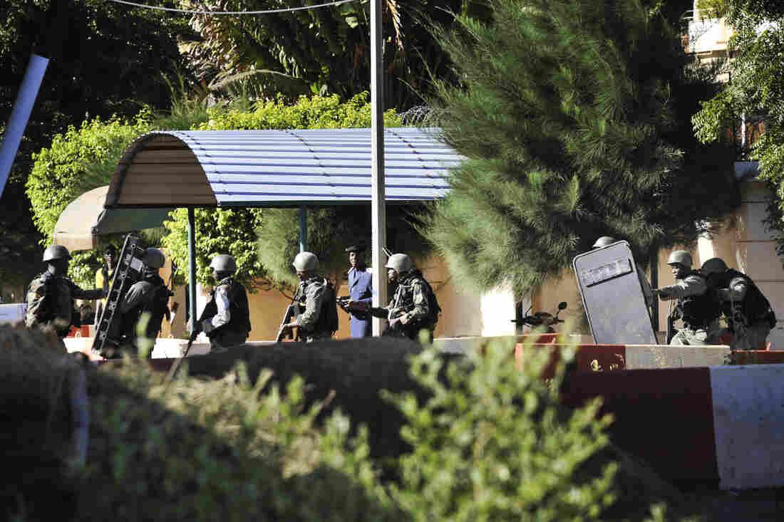 Malian troops take position outside the Radisson Blu hotel.