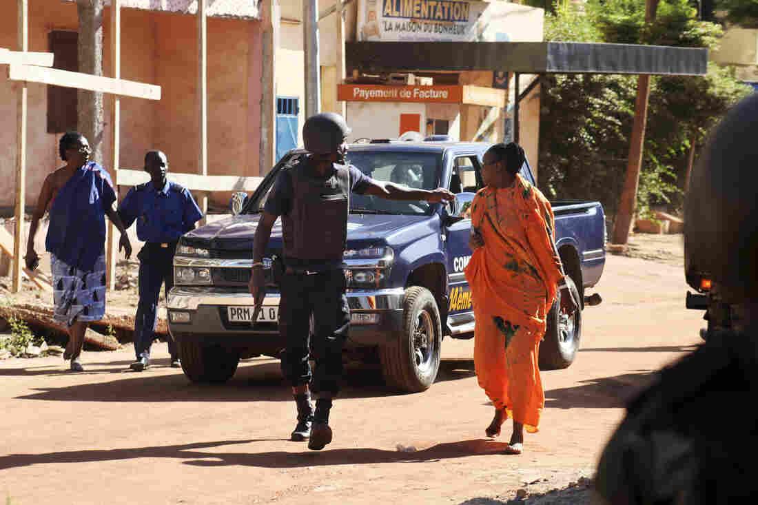 Malian security forces help two women evacuate near the Radisson Blu in Bamako.