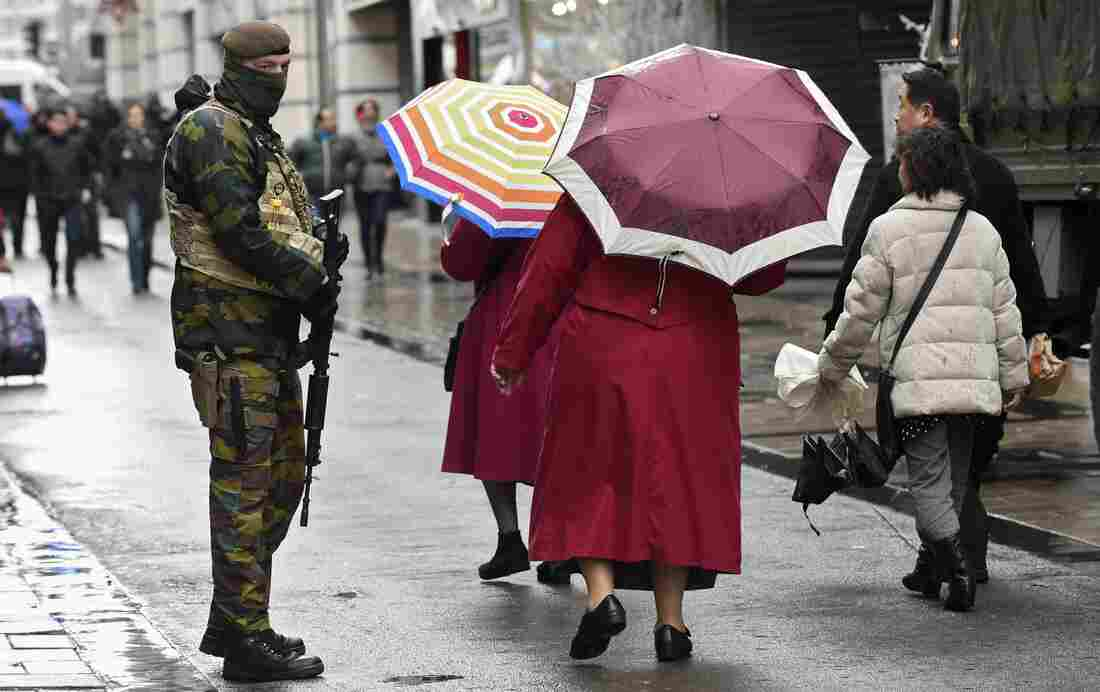 A soldier patrols outside a Brussels shopping center Saturday, after the government put the city on its highest terror alert. All metro train stations in the city are now closed.