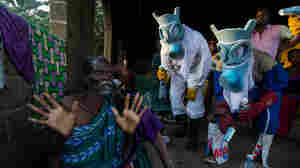 "The photographer brings a surreal touch to the epidemic that struck West Africa in photos titled ""Le Temps Ebola."" The suits worn by the people portraying health professionals evoke carnival masks and animal masks. The question the photographer ponders: ""Are these figures here to protect the people or to harm them?,"" reflecting mistrust of  medical workers in the early stages of the outbreak."