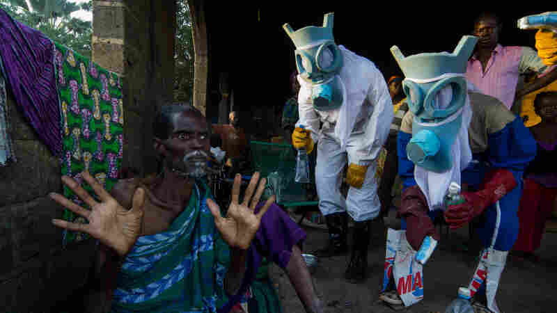 """The photographer brings a surreal touch to the epidemic that struck West Africa in photos titled """"Le Temps Ebola."""" The suits worn by the people portraying health professionals evoke carnival masks and animal masks. The question the photographer ponders: """"Are these figures here to protect the people or to harm them?,"""" reflecting mistrust of  medical workers in the early stages of the outbreak."""