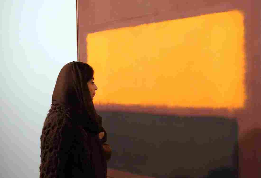 """An Iranian woman looks at the painting """"Sienna, Orange Black on Dark Brown"""" by artist Mark Rothko during the opening of an exhibition at Tehran's Museum of Contemporary Art on Nov. 20. Iran amassed a spectacular collection of modern Western art in the 1970s under Shah Reza Pahlavi, but it has rarely been on display since the 1979 Islamic Revolution."""