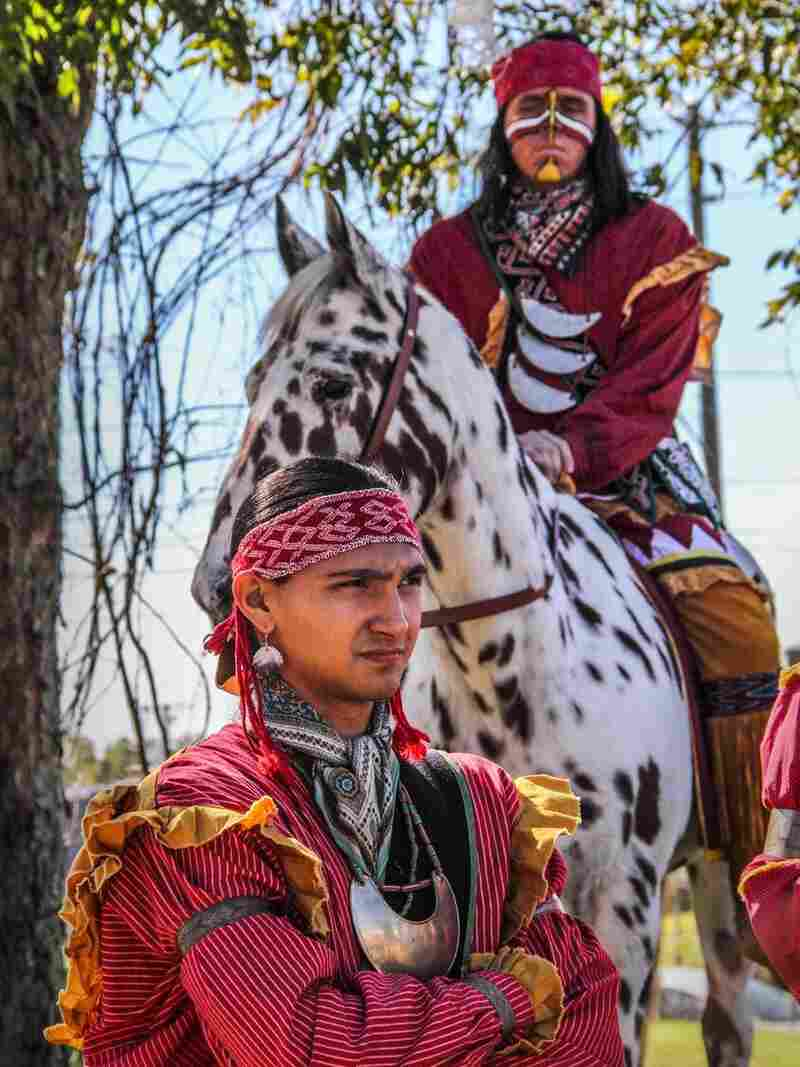Sawgrass, of Creek descent, shows off traditional adornments and attire, including silver earrings, a long shirt, and a crescent-shaped silver metal gorget at the FSU Homecoming parade. Behind him, the student playing Osceola wears a patchwork symbol for Fire. His horse Renegade isn't authentic to the real-life Osceola, impressive as he may be. He's an Appaloosa. Seminoles rode less showy horses.