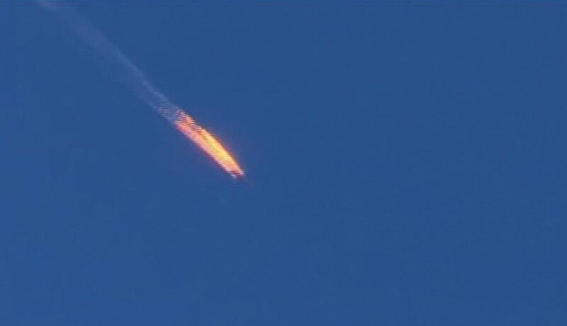 A frame grab from video on Turkey's Haberturk TV shows a Russian warplane on fire before crashing on a hill as seen from the Turkish side of its border with Syria on Tuesday. Turkey says it shot down the Russian plane because it was in its airspace. Russia says the plane was over Syria and was on a mission to bomb the Islamic State. (Uncredited/AP)