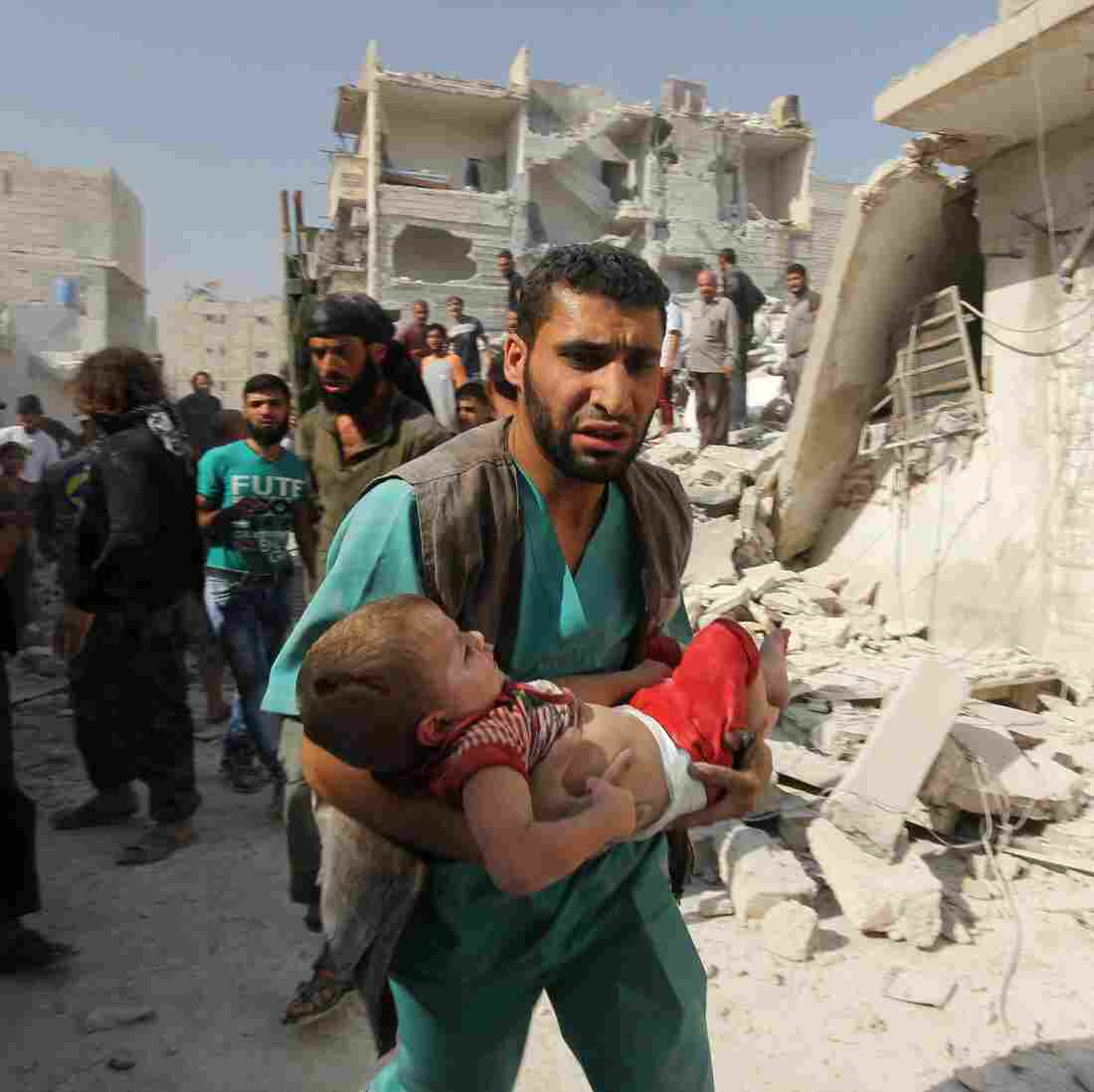 A first responder in the rebel-held city of Aleppo carries a child who was wounded in a government airstrike on Sept. 16.