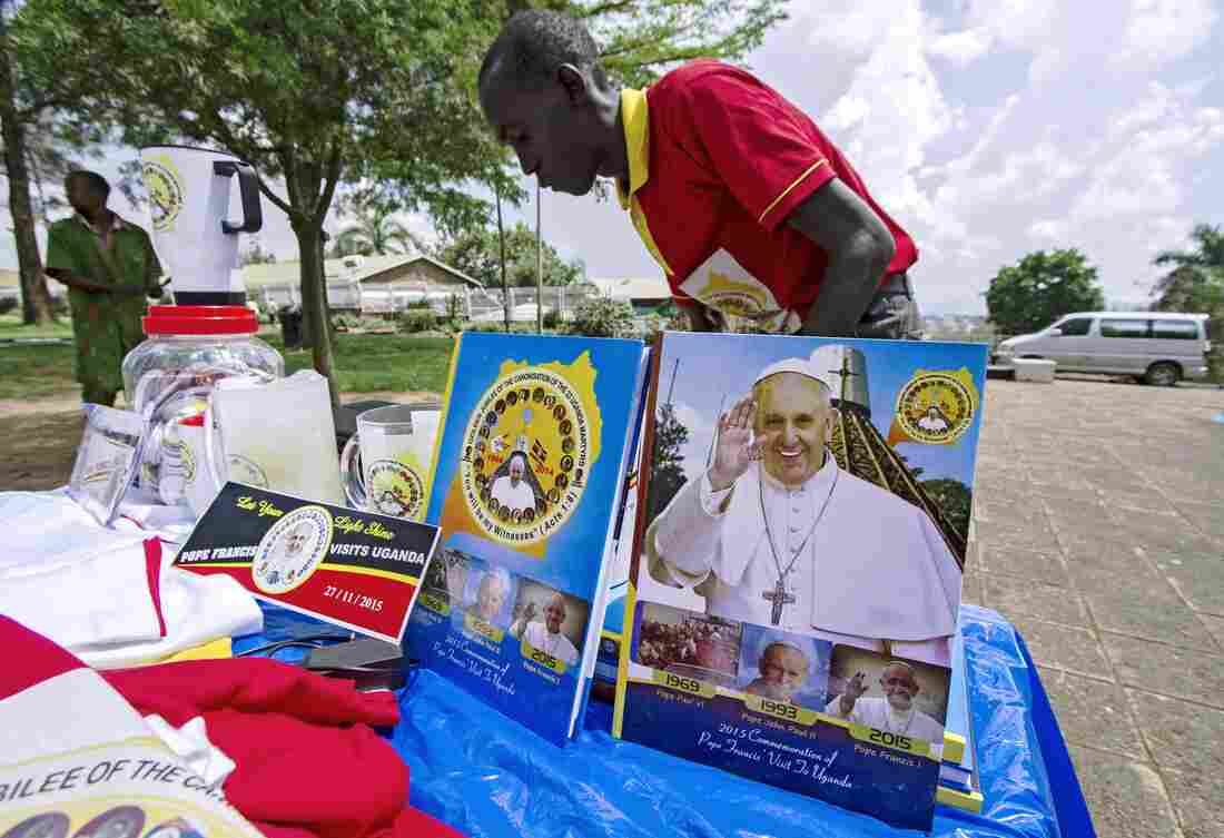 A vendor arranges portraits of Pope Francis outside of the Lubaga Cathedral in Kampala in anticipation of the papal visit.