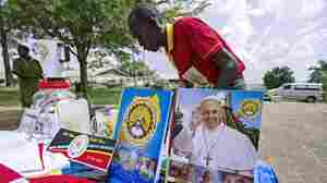 A vendor arranges portraits of Pope Francis outside the Lubaga Cathedral in Kampala, Uganda, in preparation for the papal visit.