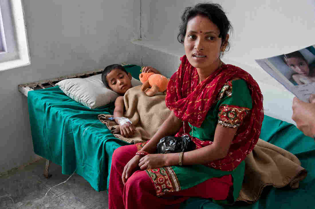 In a hospital in Dhankuta, Nepal, a mother sits with her son, who is recovering from hernia surgery.