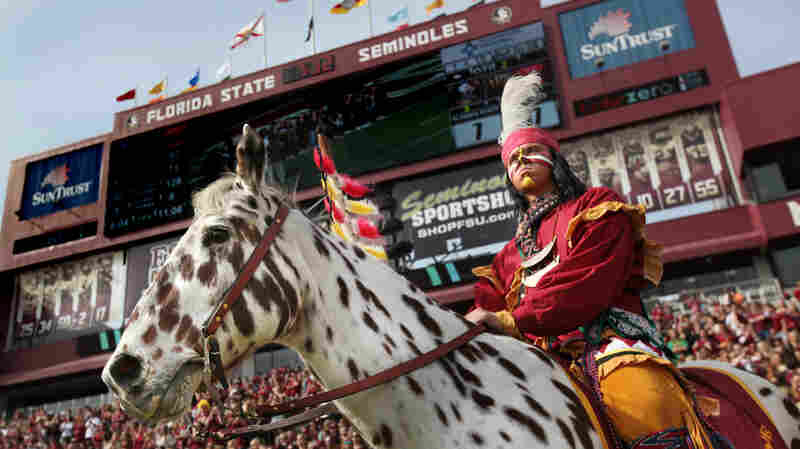 """""""Osceola"""" stands in front of a crowd at the FSU homecoming game."""