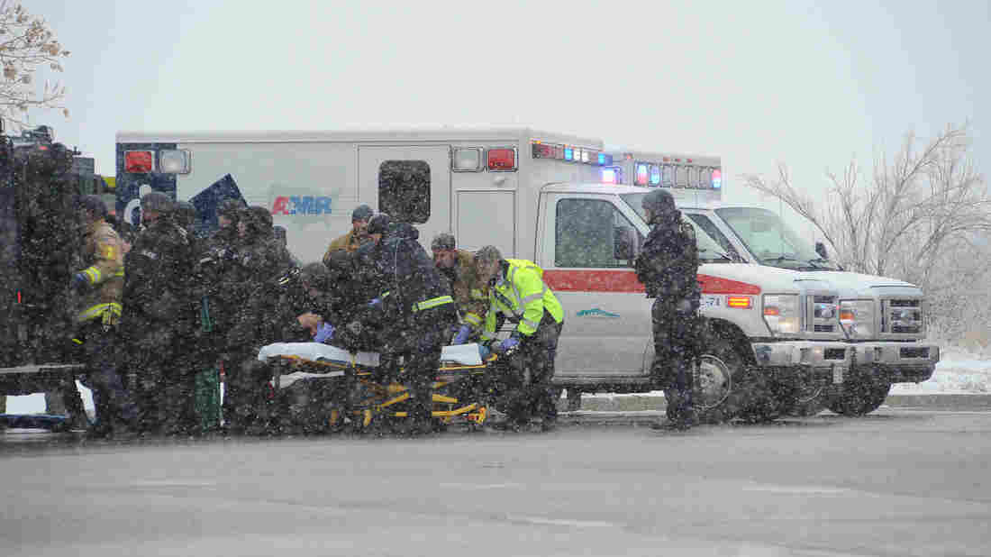An officer from the Colorado Springs K-9 Unit is transferred from a tactical vehicle to an ambulance Friday before being transported from the scene of a shooting at a Colorado Springs, Colo., Planned Parenthood clinic.