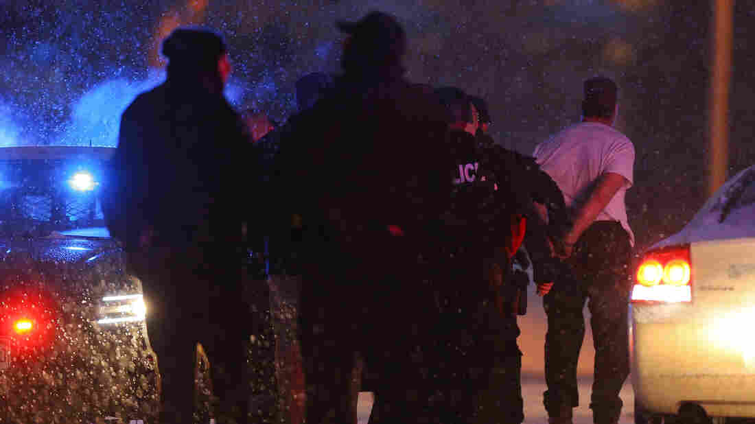 A suspect is led away in handcuffs by police during an active shooter situation Friday at a Planned Parenthood facility in Colorado Springs, Colo. Police continue to investigate the scene and are searching the building for possible explosive devices.