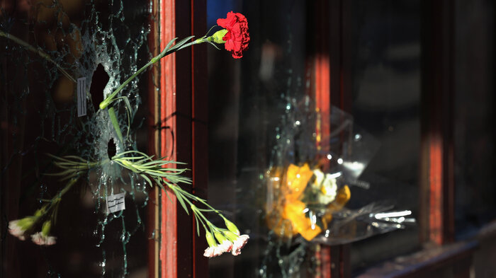 A flower is placed inside a bullet hole in the window of Le Carillon restaurant in tribute to the victims of the terror attacks on November 15 in Paris, France. (Christopher Furlong/Getty Images)