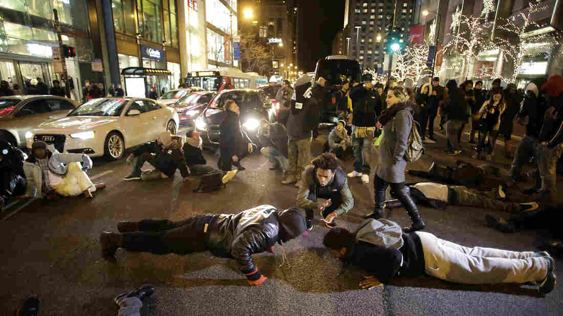 Demonstrators do push-ups Friday as others block motorists along Chicago's Michigan Avenue as they protest the shooting of Laquan McDonald who was killed by a police officer in 2014.