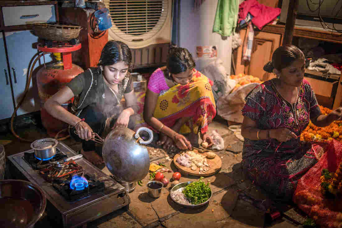Aniket's older sister, Aishwarya (left, with a cousin), prepares a meal. Her mother, Rekha Sathe (right, stringing garlands for the family business), started teaching her daughter to cook at age 10 to prepare her for married life.