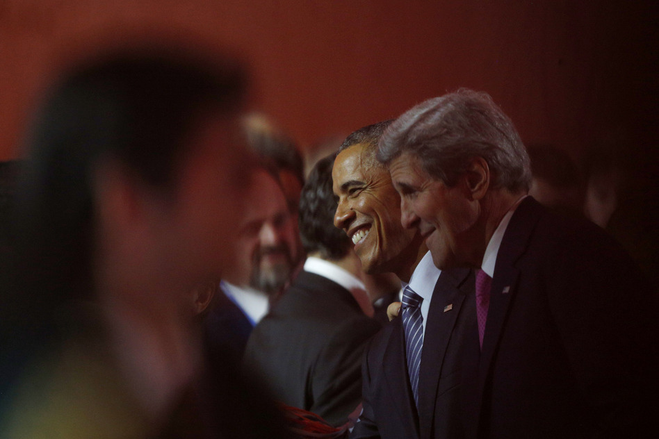 President Obama (center) and Secretary of State John Kerry (right) attend Monday's opening ceremony of the United Nations Climate Change Conference in the Paris suburb of Le Bourget. (Thibault Camus/AP)