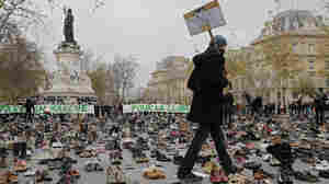 "A man walks through hundreds of pairs of shoes displayed in Paris as part of a rally called ""Paris sets off for climate"" on Sunday, Nov. 29. More than 140 world leaders are gathering around Paris for high-stakes climate talks this week."