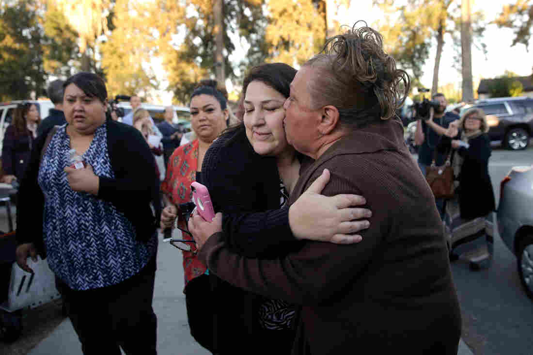 A woman, who declined to give her name, kisses her sister as they reunite at a community center in San Bernardino on Wednesday.